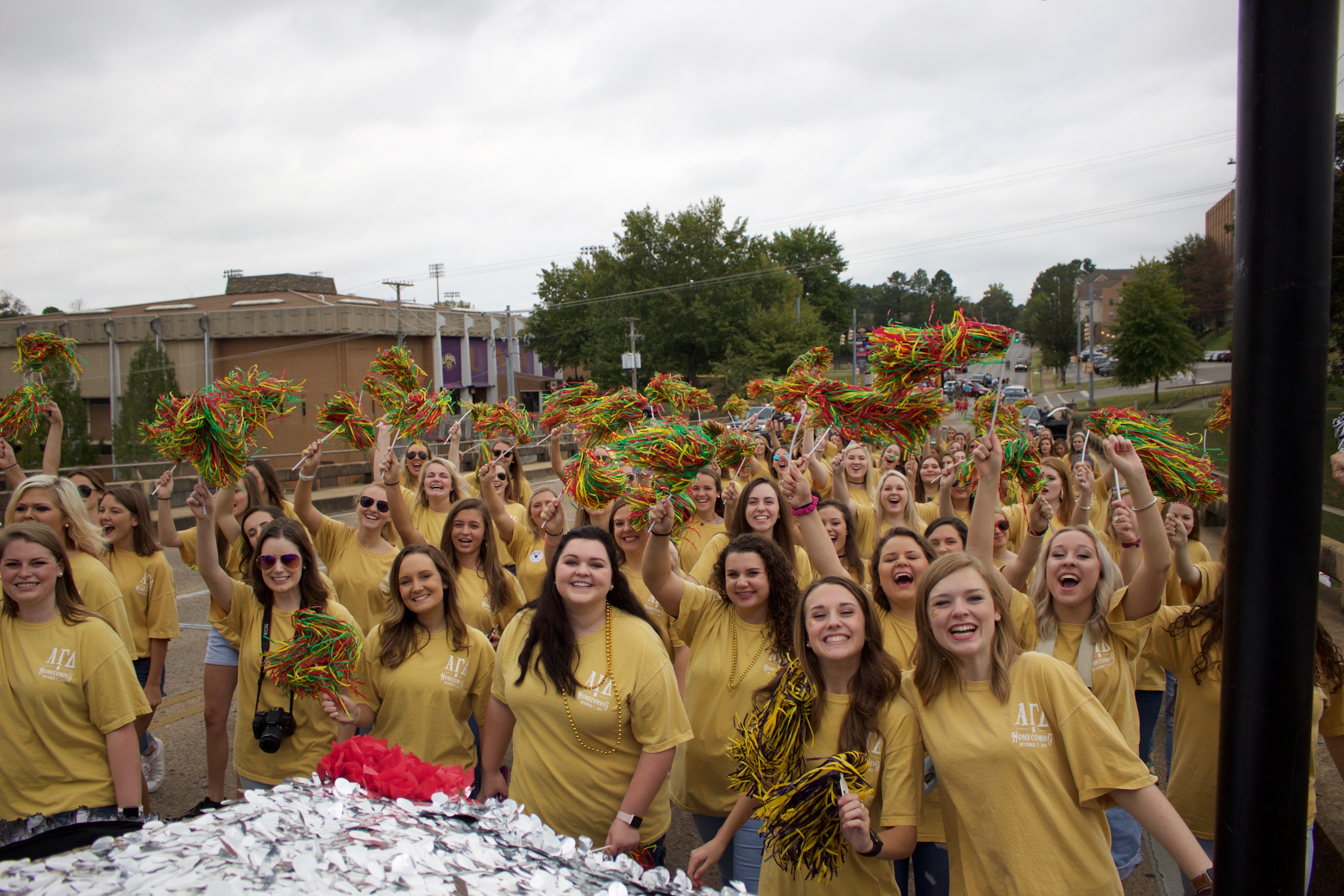 Alpha Gamma Delta members in yellow shirts cheering with green, red, and yellow poms during homecoming parade.