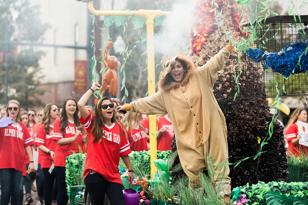 Alpha Gamma Delta member dressed in lion costume on homecoming float surrounded by women in red alpha gamma delta shirts cheering with pom poms.
