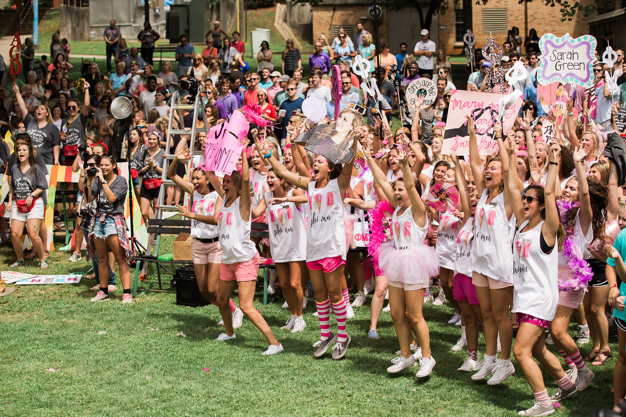 Members of Phi Mu sorority holding signs and cheering on bid day.