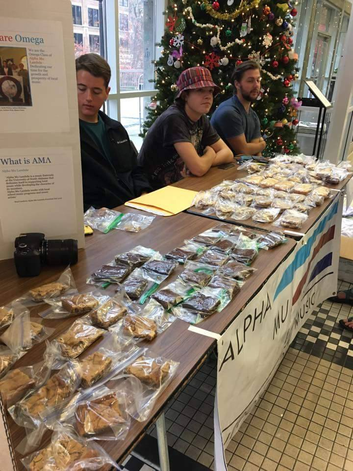 Three members of Alpha Mu Lambda sit at a table in the GUC atrium selling baked goods.