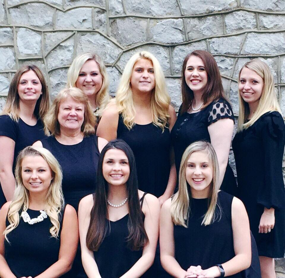Members of Nu Alpha in black dresses gathering after their induction ceremony.