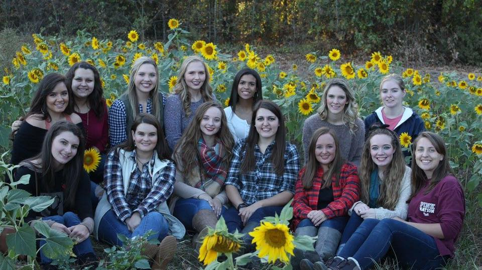 Fourteen members of Alpha Delta Chi pose for a group photo in a field of sunflowers.
