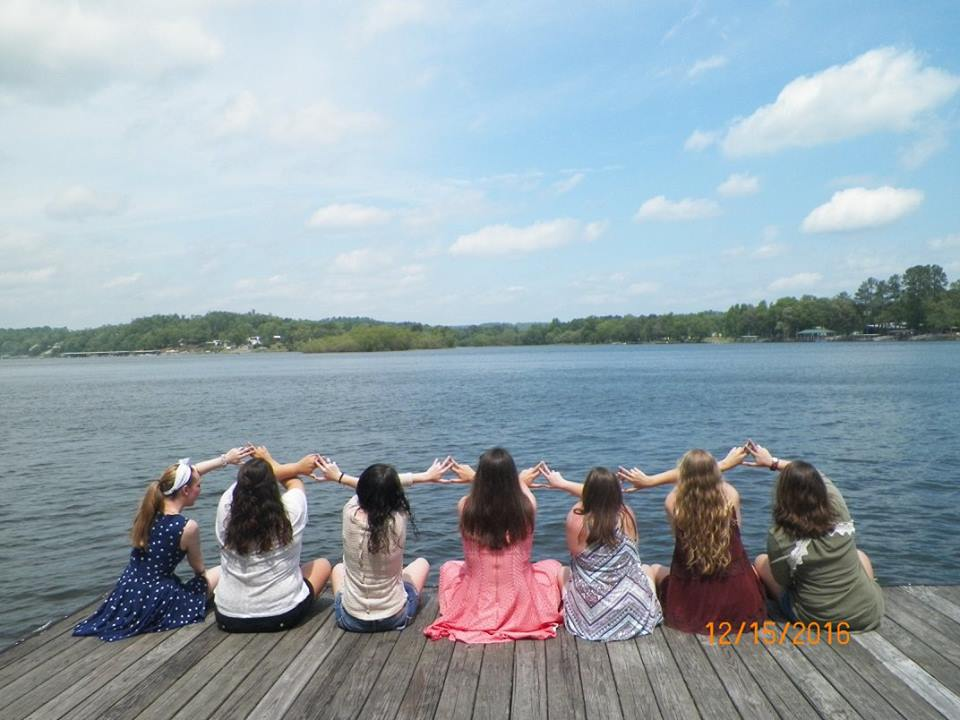 Members of Alpha Delta Chi sit on a dock looking into the water.