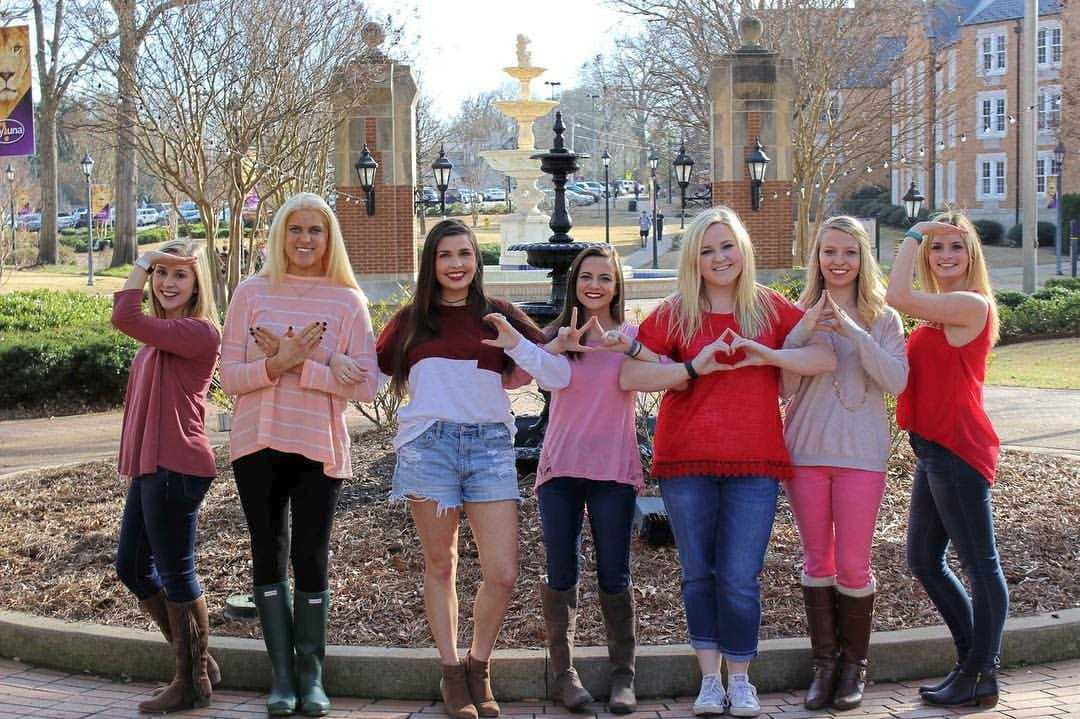 Members of Nu Alpha in varying shades of pink gather together in front of the Harrison Fountain for a photo.