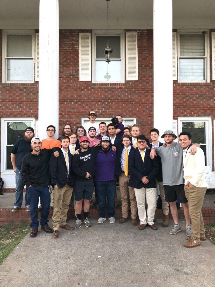 Men gathered around, posed in the front of the Pi Kappa Alpha house.