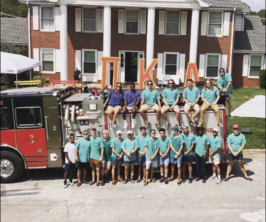 Fraternity members posed on a fire truck out front of the Pi Kappa Alpha house.